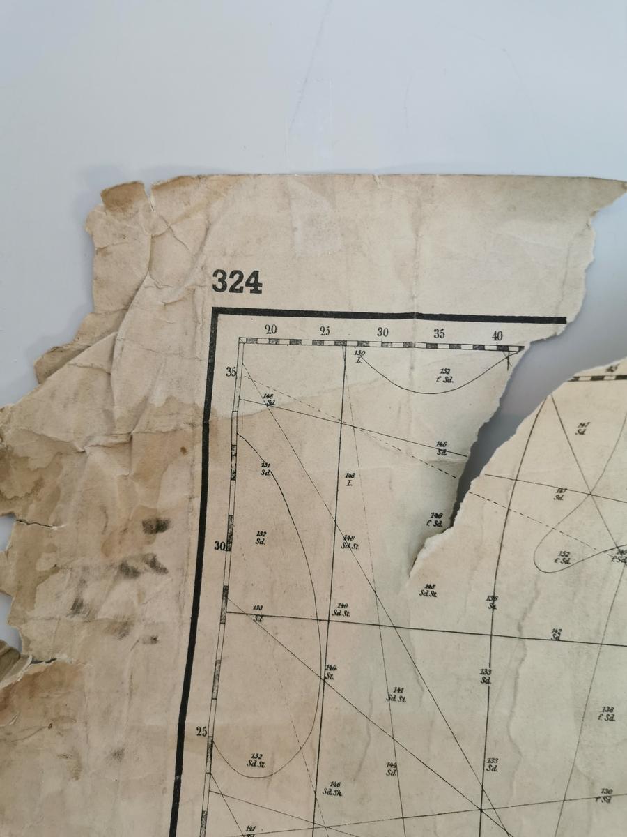 Sjøkart i målestokk 1:200,000. Kartkanten har skader, rifter og bretter. Det er to lysebrune flekker på kartet.