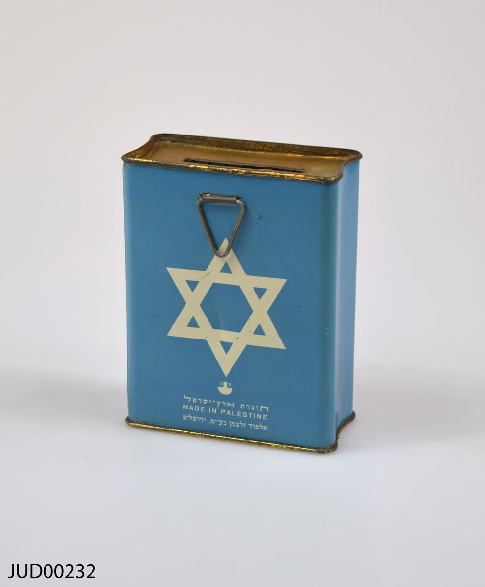Insamlingsbössa, tillverkad av plåt och sedan målad med blågrön färg. Dekorerad med vit stjärna samt hebreisk text. Låst och saknar nyckel.
