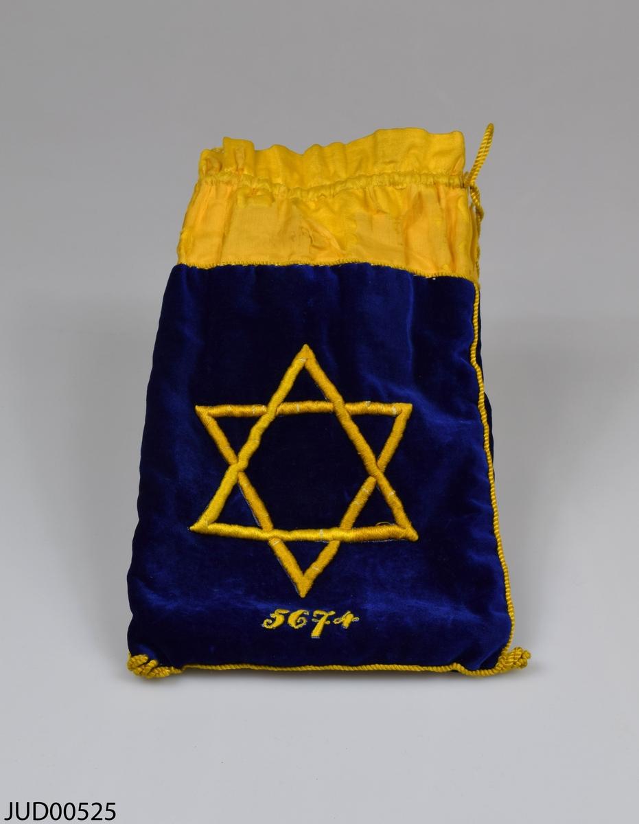Tefillinpåse tillverkad av blå sammet och gult siden. Klädd invändigt med gult sidentyg. Påsen är dekorerad med brodyr i form av en davidsstjärna och 5674 på ena sidan, samt initialer på andra sidan. I ligger två uppsättningar av tefillin.