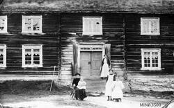 Fire kvinner, ett lite barn, foran inngangsparti digert hus.
