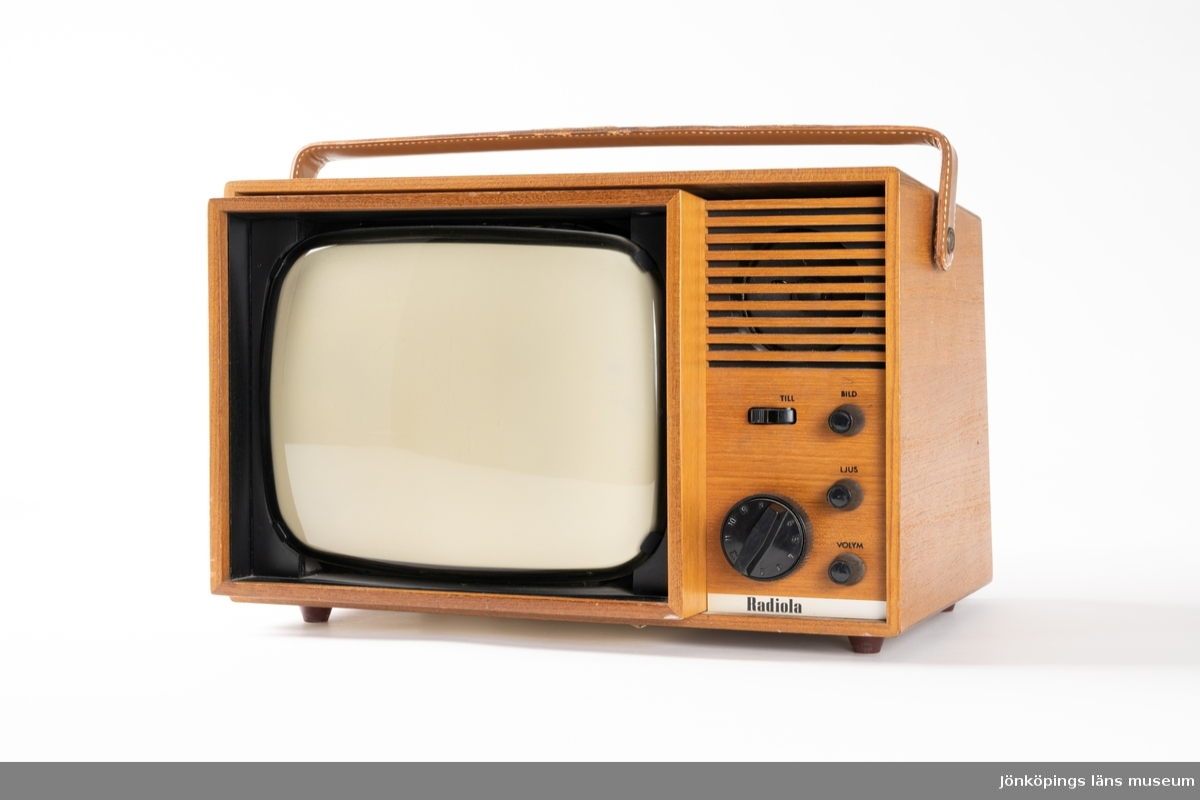 """TV-apparat, Radiola Minett Typ 8410, av teak bärbar med handtag av läder. Upptill finns en uppdragbar antenn, baktill en vit sladd. På baksidan sitter en etikett med firmanamnet: """"Karlsons RADIO TV FOTO I HUSKVARNA AB TEL. 30167-33910""""."""