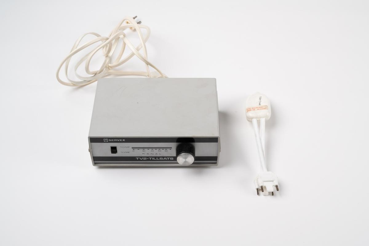 TV2-tillsats, Servex 133 2030, för kanal 2. Grå plastlåda med olika sladdar för antenner och nätanslutning. Ratt att ställa in kanaler med.  Objekt JM.54963 hör troligen till TV2-tillsatsen.