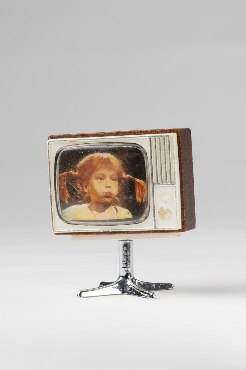 TV till dockskåp, av brunt trä, vit plast på fram- och baksida. Fot av silverfärgad plast. I rutan färgfoto av Pippi Långstrump.
