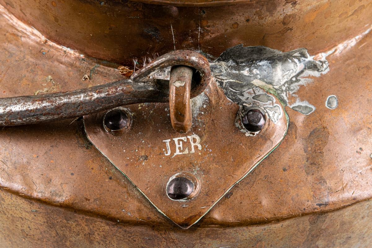 """Spann med lock, koppar. Handtag med triangulära bladformiga fästen. Stämpel: """" J E R""""  på ett fäste."""