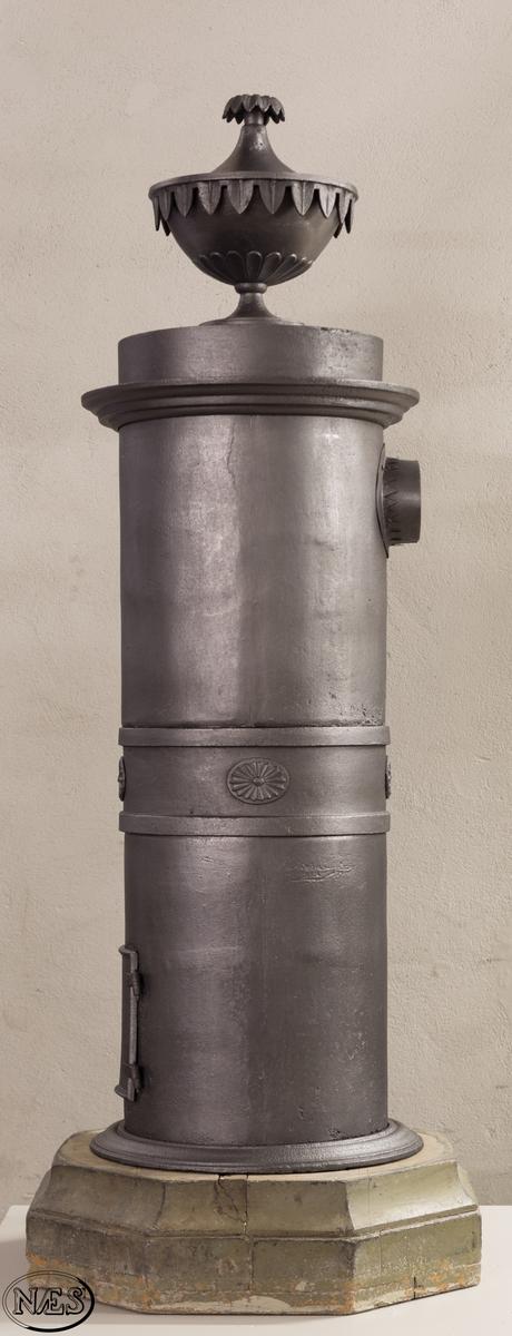 Rund ovn på tresokkel. Pidestalovnen står på en åttekantet sokkel. Profilert sirkelformet bunnplate og firkantet ovnsluke. Oven er delt opp i tre seksjoner, hvor den minste er plassert i midten med rosetter som er klinket fast. Den sirkelformede bunnplaten avsluttes med en profil ytterst. Profilert gesims mot toppen. Øverst står en vase med lokk. Ellers har ovnen store glatte flater.