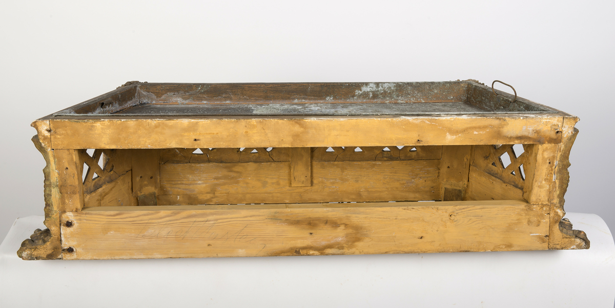 Lavt konsollbord med utskårne elementer; ett kvinnehode på hvert hjørne. Rik rokokkodekor som er forgyldt. Metallbakke nedfelt på toppen. Antagelig for blomsterdekorasjon.