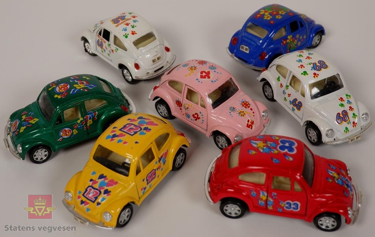 Miniatyrmodeller av Volkswagen Type 1. Syv biler med hovedfargene gul, hvit, rød, grønn, blå og rosa. Bilene er laget hovedsakelig i metall med plastunderstell og detaljer.