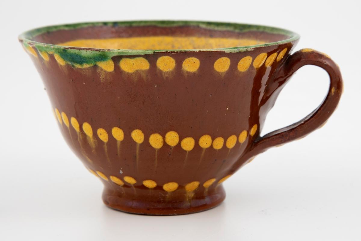 Kopp med hank og underskåler.  Rødbrunt leirgods med grønn rand rundt munningen. Dekorert med gule prikker og linjer