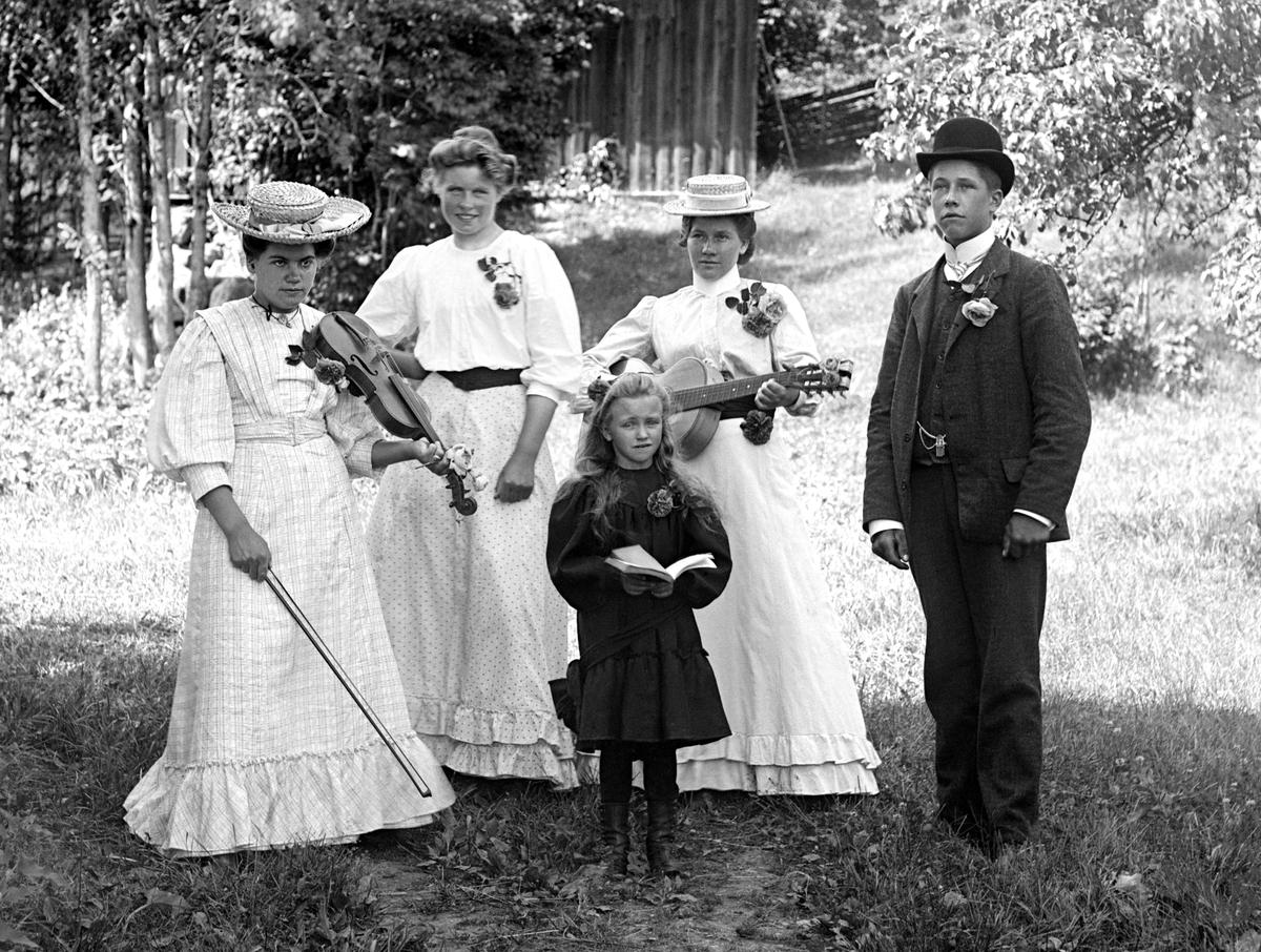 I trädgården hos fotograf Emil Durling har ett musikaliskt sällskap samlats. Stående näst längst till vänster är Ester Karlsson - mer känd som Ester Bölja Bergström efter ett taget tillnamn och giftermål.   Anm: Identiteten av de övriga personerna har ej kunnat styrkas.