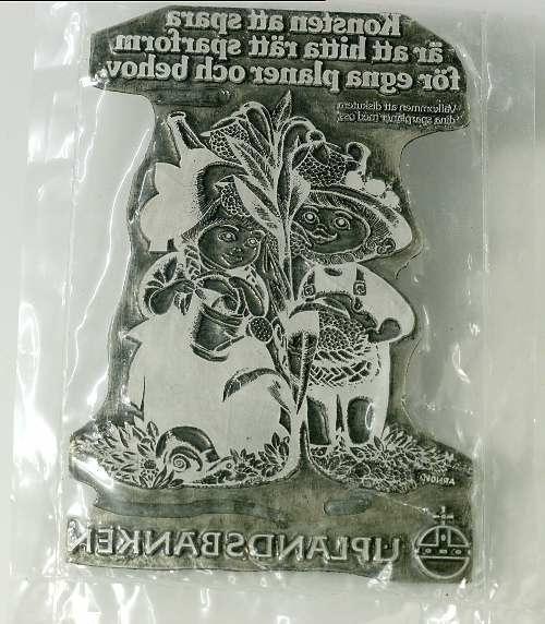 Trycktyp av bly. Text: Konsten att spara är att hitta sparform för egna pengar och behov / (finstilt text) / figur av Hans Arnold / UPLANDSBANKEN. Inslagen i plast.