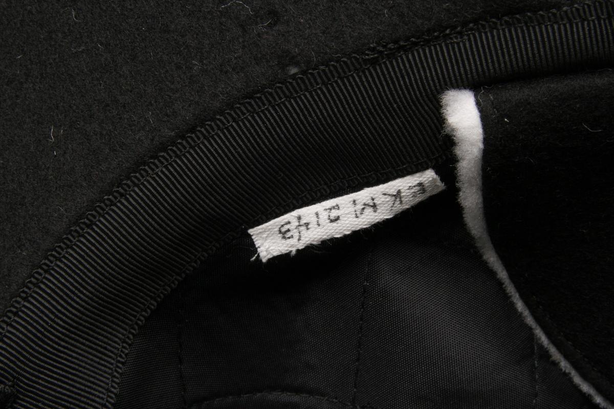 Østerdalslue med skygge og nedfellbare ørelapper. Sydd i svart ullklede.