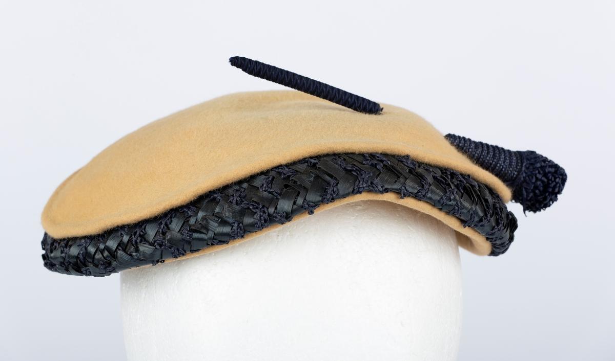 Flat liten hatt med kant av blå tråd og og bast. Brukt av Olga Ambjørnrud under 2. verdenskrig