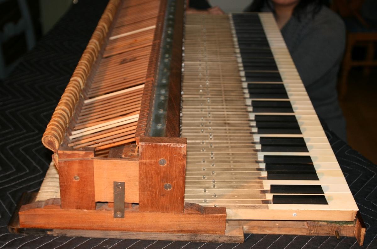 """Omfang: CC-f'''' (6 oktaver + kvart = 6 ½ oktav) Flygelinstrument med mahogany(finer?)kasse. Lås i bronse/ messing, tredelt lokk, massiv mahogni.  Strenger/klangbunn CC-FF to str/kor, omspunnet gul messing FF#-G# tre str/kor, flat gul messing A-f'''', tre str/kor, jern [malcom Rose B(?)] Delt stol ved G#/A; Backpinning gjennemgående.  Klangbunn med ornamentert utsaget triangel i basshjørne mot stemmestokk. Årretning, ca 5 grader clockwise fra bakre langsarge. 4 """"gap spacer"""" i metall samt to jernbalker som holder stemmestokk og klangbunn ifra hverandre. Hel storbunn, ingen inspeksjon under klangbunnen.  Mekanikk Hammere med lærovertrekk. Dempere til og med a''' (type én, med enkel springer – som på et cembelo –a''; type to med demperfilt på ekstensjonsarm mot sadellist, se bilde bb'' – a'''. Rektangulære stemmeskruer (oblong) uten hull.  Pedaler: To stykk. Venster: Due corda, med løftbar knapp t.h. for klavituret slik at UNA cord kan brukes [vanlig på typen, ifølge Odd Aanstad] Høyre: Demperløft [split i to: venstre del løfter bass; høyre løfter diskant] [NB! Nå ombygget til kun alle samtidig (mekanikk i diskant)."""