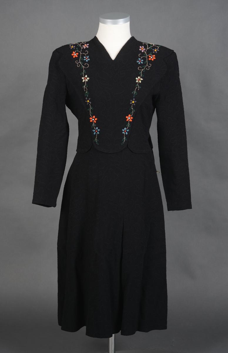 Svart kjole med lange ermer og perlebroderi på overdel framstykke. Håndsydde perlebroderier med motiv av blomster. Kjolen er avtatt i livet. Åpning MB som lukkes med 6 trekte knapper og passepoilerte knapphull. Glidelås i venstre side. Skulderputer, V-rigningen i halsen foran. skjørtet er sammensydd av 7 høyder. Nede på ermene er det liten splitt som lukkes med 3 små trekte knapper og rouleau hemper. Påsydd silkestoff for opplegg nederst på skjørtet. Opplegg og overkasting er gjort for hånd.