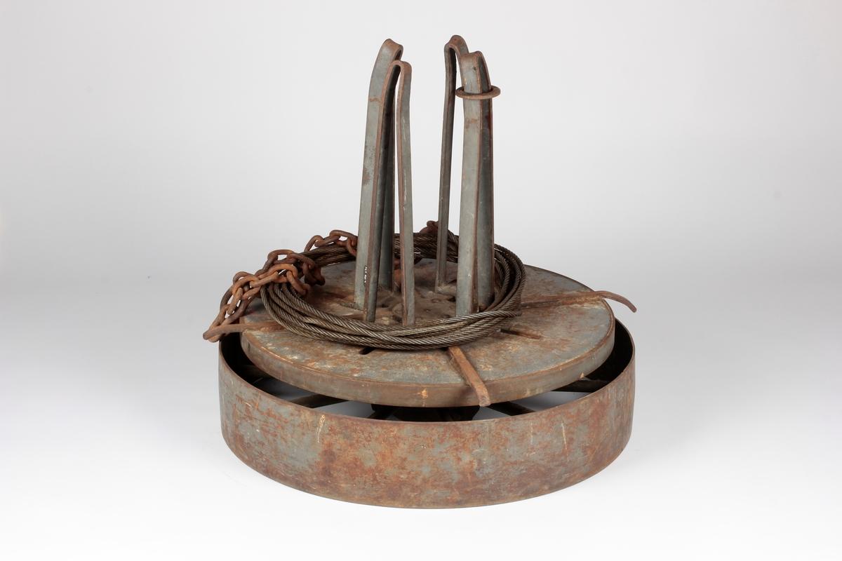 Rund sokkel av stålplate med eiker. Roterende topp med bunnplate og fire oppstående bøyler i stål.