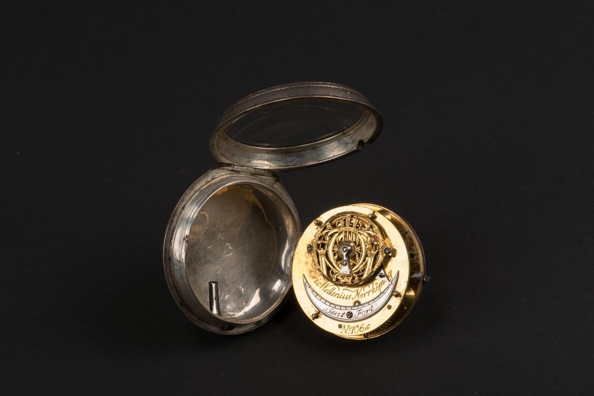 Runt fickur med spindelverk.  Boetten är tillvekat av silver och locket av glas. Den är stämplad på insidan med: E W (Erik Wellenius), Norrköpings stadsstämpel samt årsstämpel Y (1781). Boetten är försedd med en hållare för klockkedja. Den vita urtavlan av emalj har svarta romerska siffror samt markeringar för minuter. Uppdraget sitter vid IIII. Det finns en tim- och en minutvisare, de är tillverkade i gulmetall. Verket är graverat med: Erik Wellenius Norrköping No 306.
