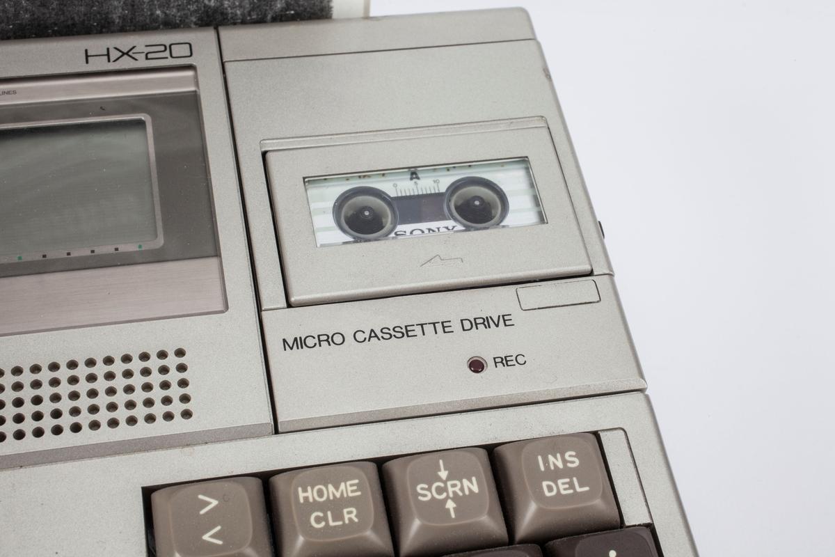 En bærbar datamaskin med en liten skjerm, tastatur, spiller for mikrokassett og innebygd miniprinter. Det ligger en kastett i spilleren.
