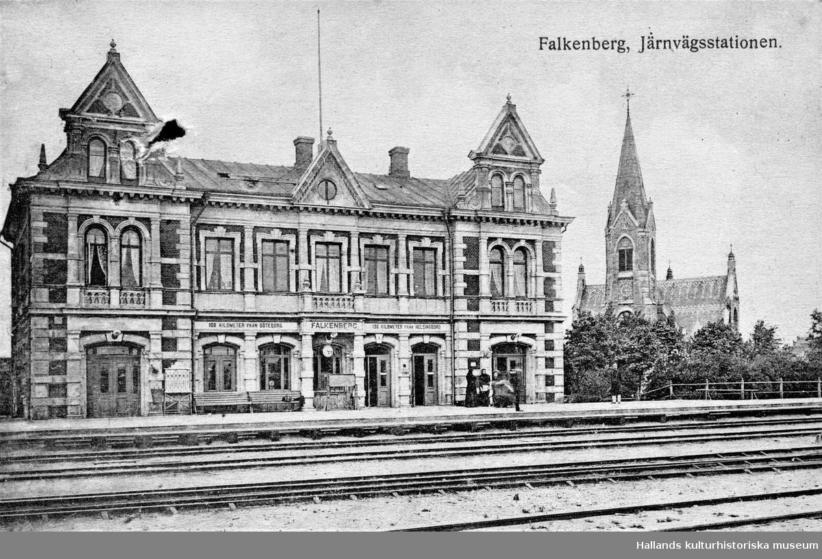 """Vykort, """"Falkenberg. Järnvägsstationen"""". Till höger ses stadens moderna kyrka från 1892. På stationshusen angavs ofta avstånd till andra orter. Här upplyses resenärerna om att de är 108 km från Göteborg och 136 km från Helsingborg."""