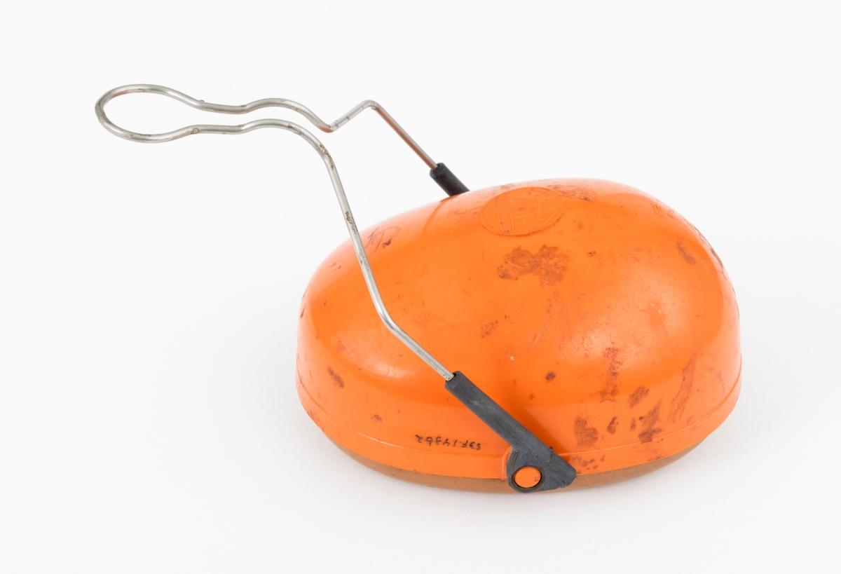 Hørselvern, øreklokke, av typen Peltor H7. Hørselvernet, øreklokka, består av en ovalt formet halvkule av støpt plast med innlegg av skomgummi og en væskefylt tetningsring som omslutter brukerens øre. Innleggene og tetningsringene er utskiftbare. Det er festet en metallbøyle  med glidefeste for høyderegulering til øreklokka. Øreklokkas metallbøyle monteres på hjelmfestet.
