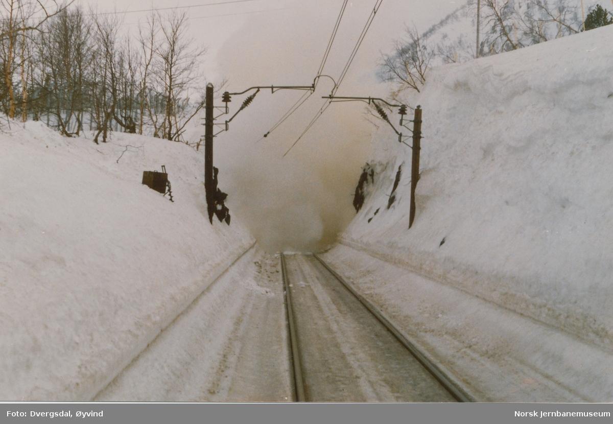 Snørydding ved Fjellberg tunnel ved Haugastøl. En enorm snøskavl hadde bygget seg opp over tunnelmunningen. NSBs Ledningsavdeling trakk til side kjøreledningen hvoretter skavlen ble sprengt med dynamitt, og deretter ryddet med roterende snøplog