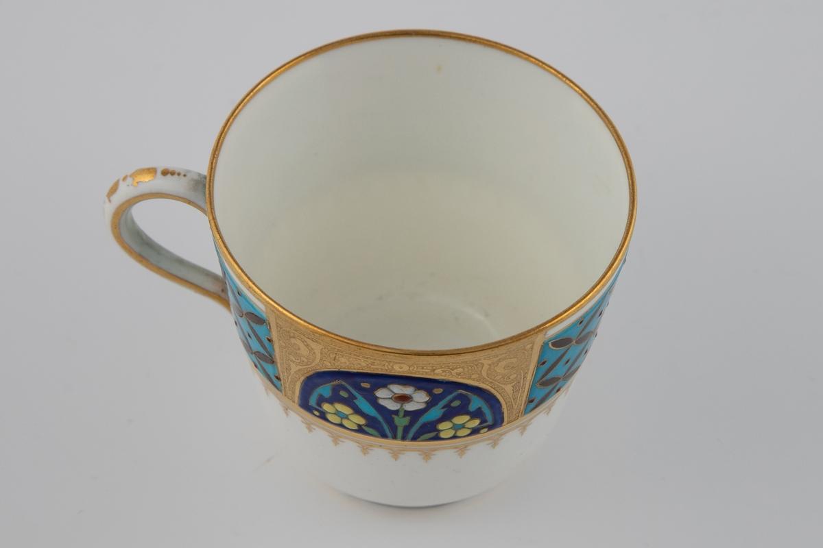 Kaffekopp med hank. Koppen har et middelalderinspirert mønster på øvre del av korpus, hvor kombinasjonen av overglasurmaling og forgylling skal minne om celleemalje (jf. cloisonné). Dekoren består av to felter med blomster i hvitt, gult, rødt og turkis på blå bunn, omgitt av en forgylt bue. De to andre feltene består av et rutenett med røde, firgrenede  blader på turkis bunn. Samtlige dekorelementer er omgitt av forgylte konturlinjer. Overgangen til nedre del av korpus er markert med en ornamentell bord.