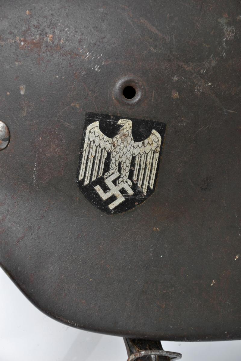Militærhjelm i stål med regulerbar polstring i skinn og lærreim. På venstre side av hjelmen er et merke i sølv og sort av den tyske ørn og hakekorset.