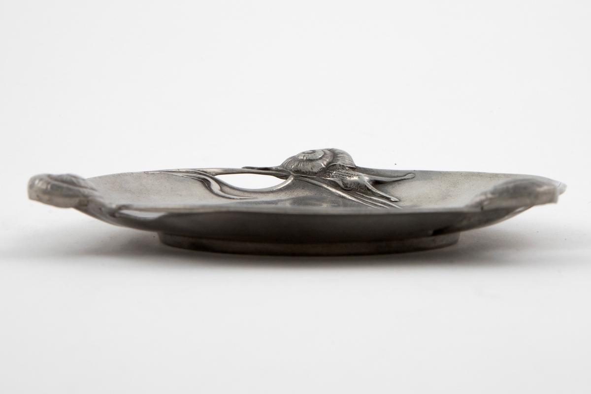 Sirkulær skål i tinn, som hviler på en lav fotkant. Noe fordypet midtparti, langs kanten gjennombrutte partier samt snegler i høyt relieff. I midten av skålen er det fremstilt d organisk ornamentikk i lavt relieff.