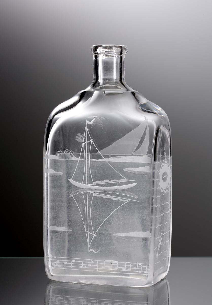 Brännvinskaraff, rektangulär modell. Graverat havsmotiv med segelbåt, med en brännvinsflaska i lina efter båten. På karaffens frånsida en graverad segelbåt och under den en notrad.