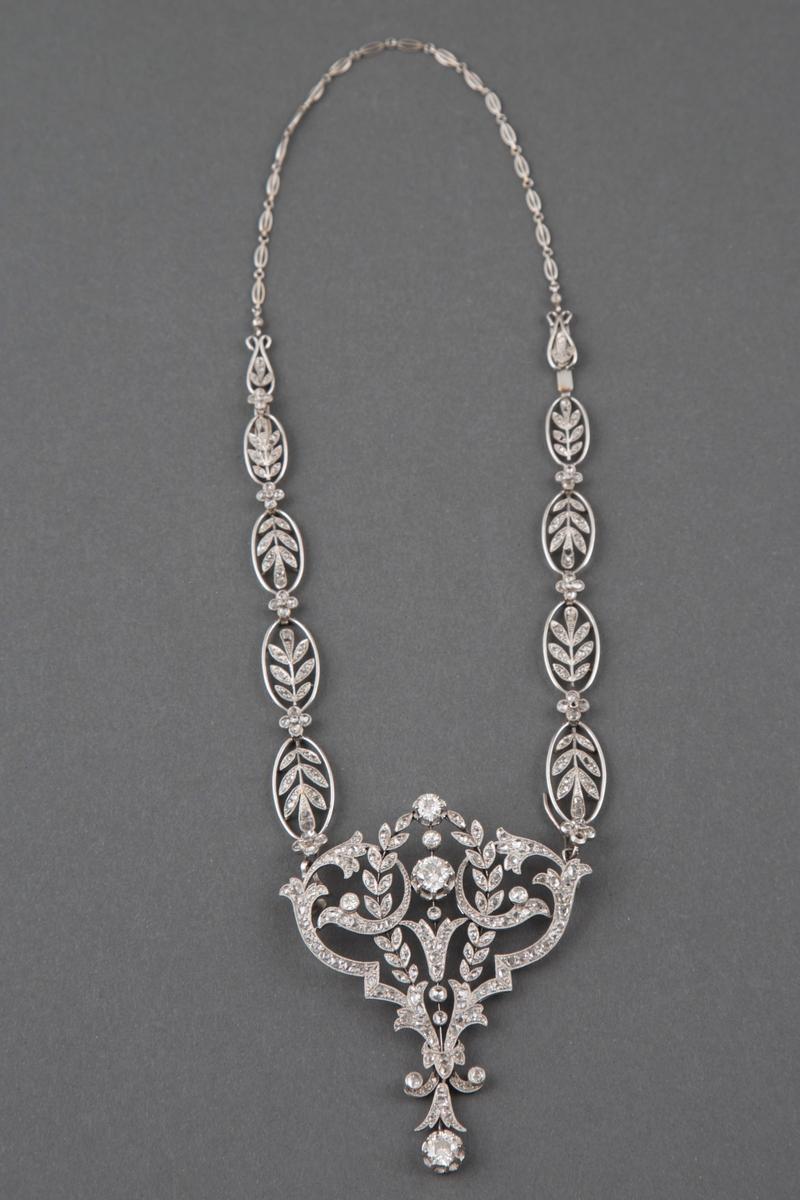 Halssmykke i platina og diamanter i originaleske. Kjedet består av ovaler med bladranker fylt med diamanter og små diamantblomster imellom. Anhenget er i hjerteform med blomster- og bladornamenter fylt med diamanter, samt runde innfattede diamanter i forskjellig størrelse.
