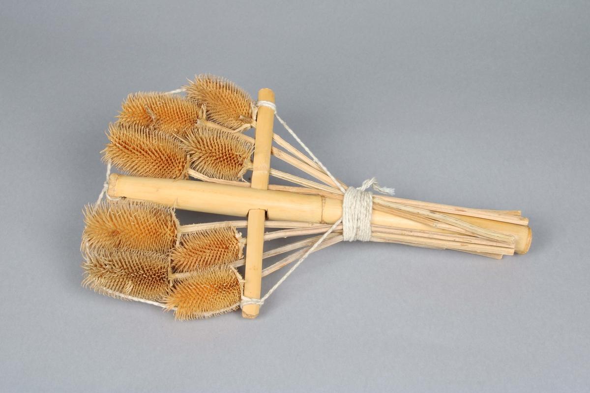 Korsformad ställning av bamburör, på vilken 8 kardborrar med stjälk, bundits fast med bomulls-snöre.  Kardborrar användes tidigare vid maskinell ruggning av kardgarnstyger. Se ruggmaskin BM 46181.  Inköpt i samband med utställningen Mayaindianernas liv 1/18-1976 - 15/2-1976 på Borås Museum.