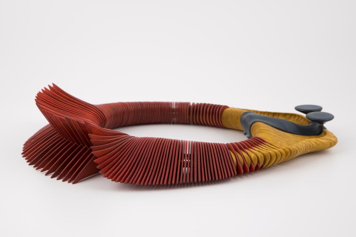 Stor oval klave i beiset tre med et organisk uttrykk. Klaven er satt sammen av treskiver i forskjellige former. Avstanden mellom treskivene skapes av små messingskiver.