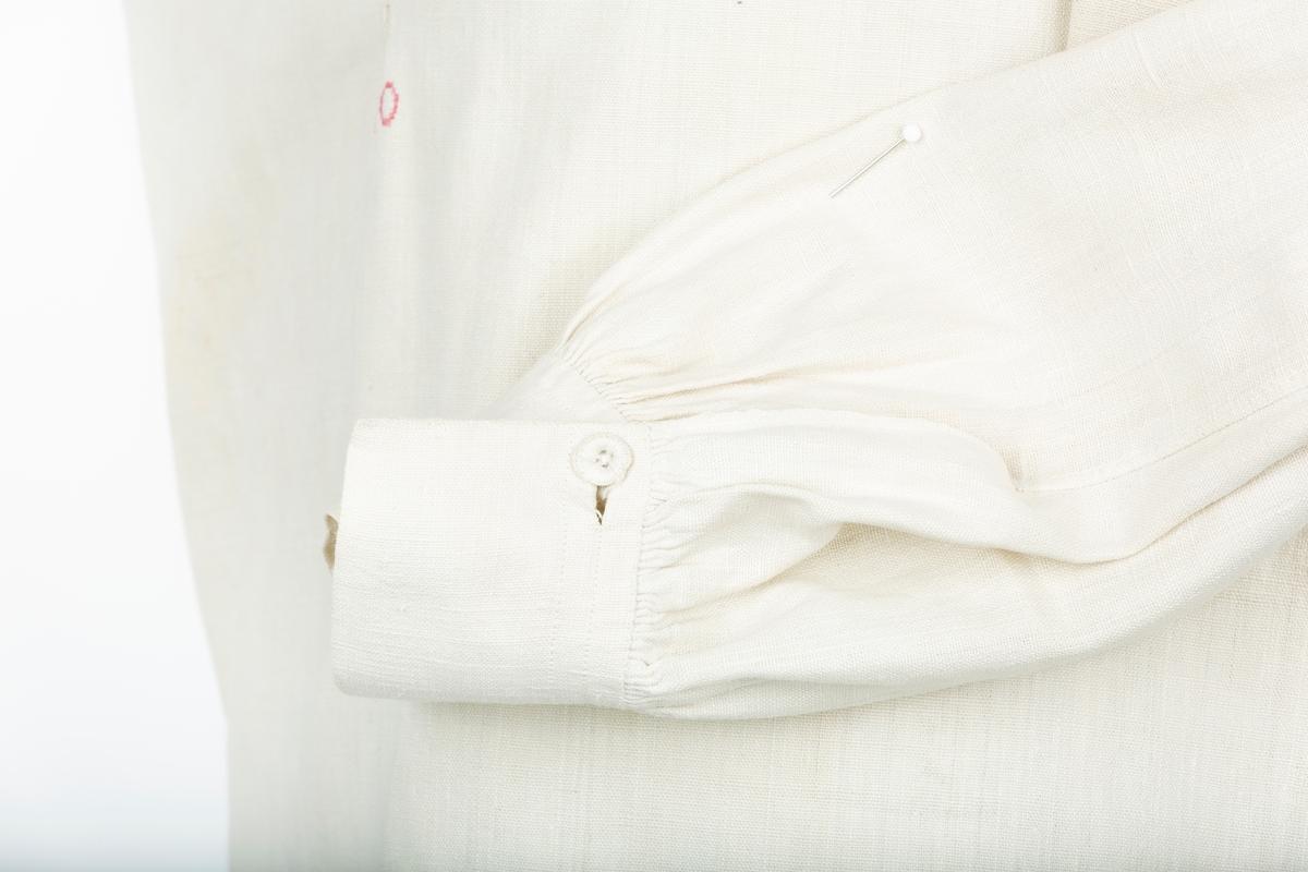 Manns-skjorte. Rett lang skjorte, lange sidesplitter, lang halssplitt, kiler ved skulder og ved armhule,  Krage, vide ermer rynket til mansjett. Under halssplitten er bokstavene  A.O brodert med røde korssting.