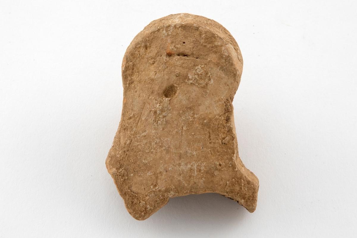 Fragment av figurin, utformet som et hult kvinnehode i terrakotta. Grågult gods.