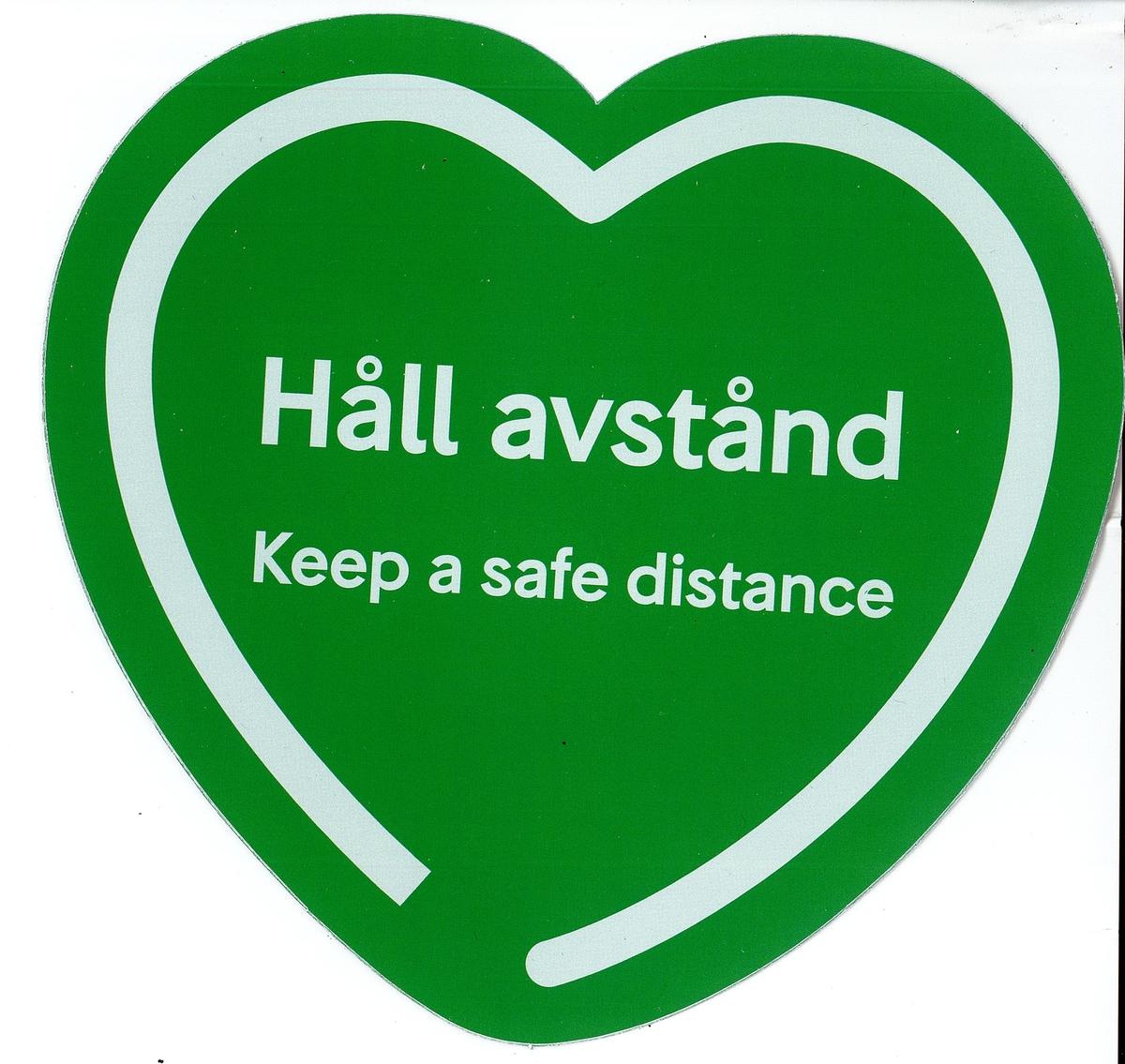 """Grön hjärtformad klisterdekal med texten """"Håll avstånd Keep a distance"""". Vit kant runt texten som följer hjärtats form men är öppen nedtill. Vit baksida."""