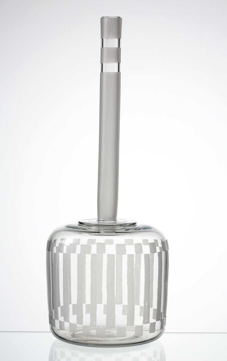 Flaska med cylindrisk buk med smal hög hals. Buken graverad med ränder och rutor. Tre graverade partier runt halsen.