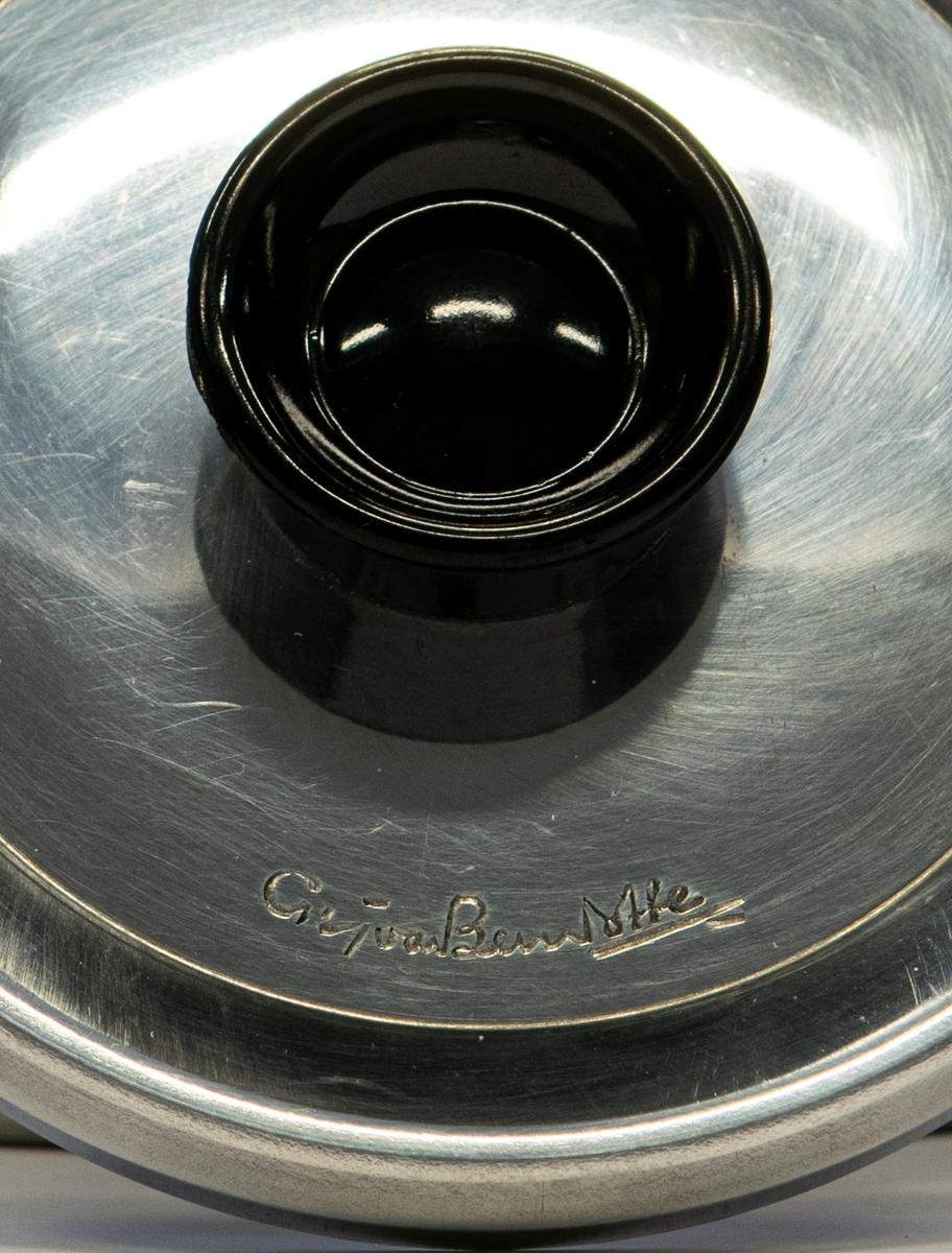 """Kaffepanna i polerad aluminium med svart handtag och knopp. 2,5 liter. Locket har formgivarens signatur. I originalförpackning av papp.  """"Moderna kök kaffepanna - Design Sigvard Bernadotte"""""""