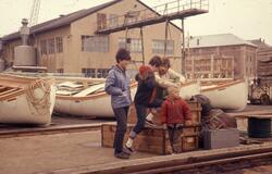 Felt 1967. Hjemtransport. Havn med båter. Kasser Feltutstyr