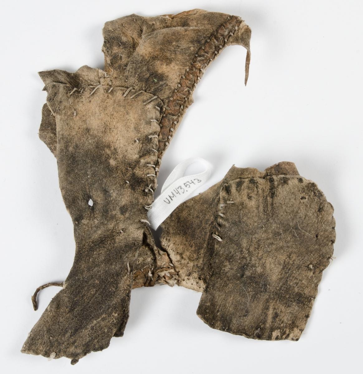 Fragment av pälsplagg. Eventuellt del av ärmhål, sidostycke och bakstycke. Osäkert vad det varit del av för plagg.