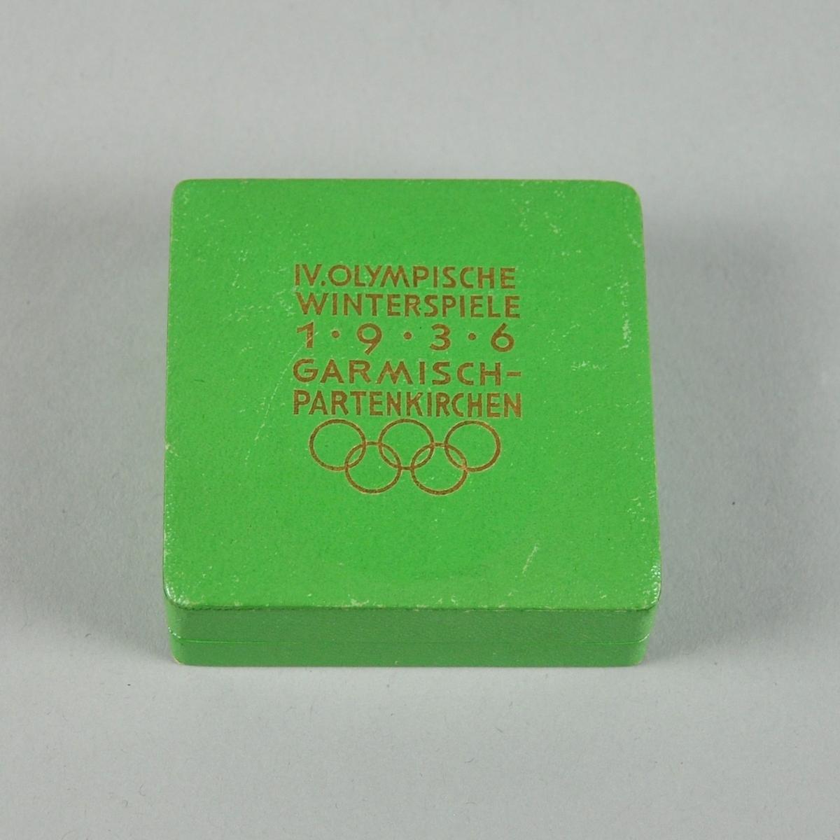 Grønn eske av kartong med tekst og de olympiske ringer i gull på lokket.