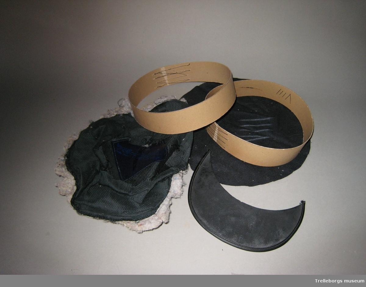 Två sjöofficersmössor. Mössorna är inte färdiga uttan ligger i delar. Delarna består av två stommar i papp, blå filt samt foder och stoppning som är ihopsatta.