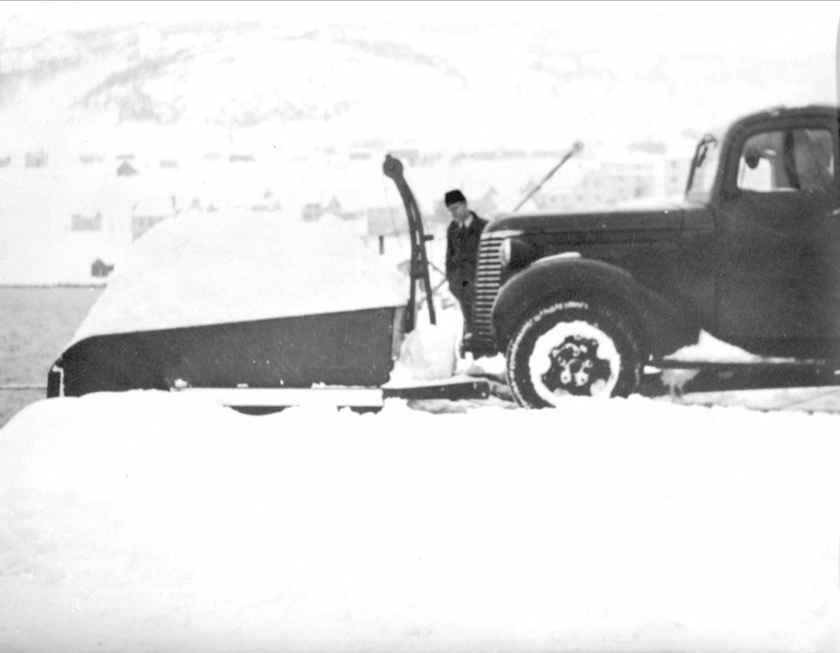 Lastebil med frontmontert snøskuffe.