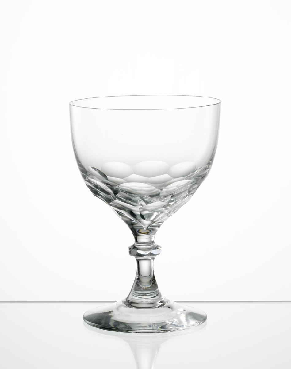 Vitvinsglas, klotsegmentformad kupa insvängd mot botten. Fasettslipade fjäll på kupans nedre del. Knappben med slät fot.