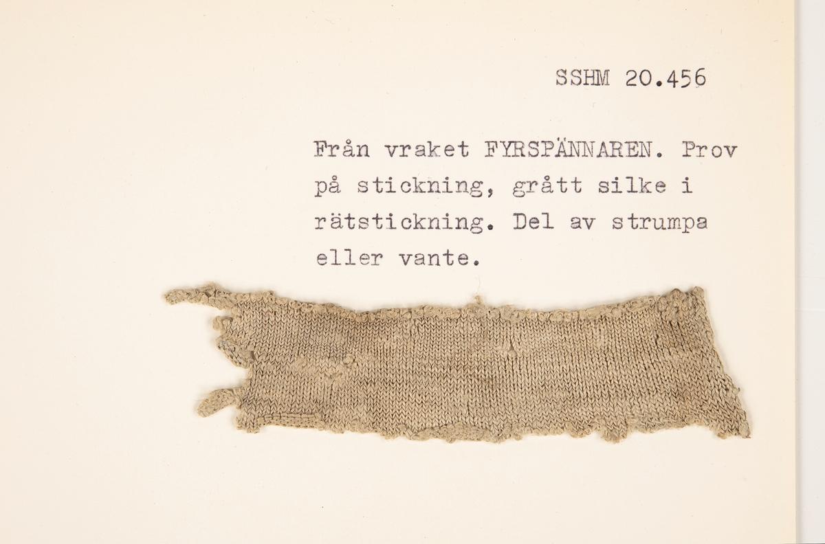 Fragment av grått silke, rätstickning.