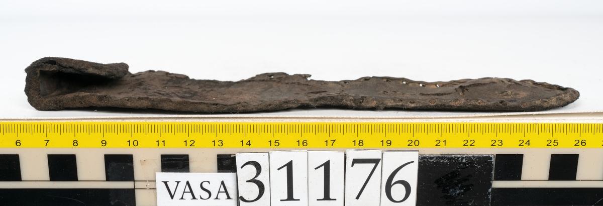 Delar från skobotten. En sula, fyndnummer 31176. Längs med ytterkanten löper hål efter stygn med kvarsittande tråd. På sulans ovansida, narvsida, finns avtryck efter bindtråden. Vid hälpartiet finns hål efter träpligg. En del av en klack, fyndnummer 31176:1. Klacken består av fem klacklappar varav en ligger löst ovanpå de andra. På undersidan finns kvarsittande träpligg. Klacken är snedsliten. Ett bakre parti och ett främre parti av en sula. Den bakre delen av sulan, fyndnummer 31176:2, har en ritsad skåra som löper från hälen och fram mot partiet för hålfoten. Längs med ytterkanterna löper hål efter träpligg och stygn. I sulans hälparti finns kvarsittande träpligg. Ytterkanterna är delvist fragmentariska.