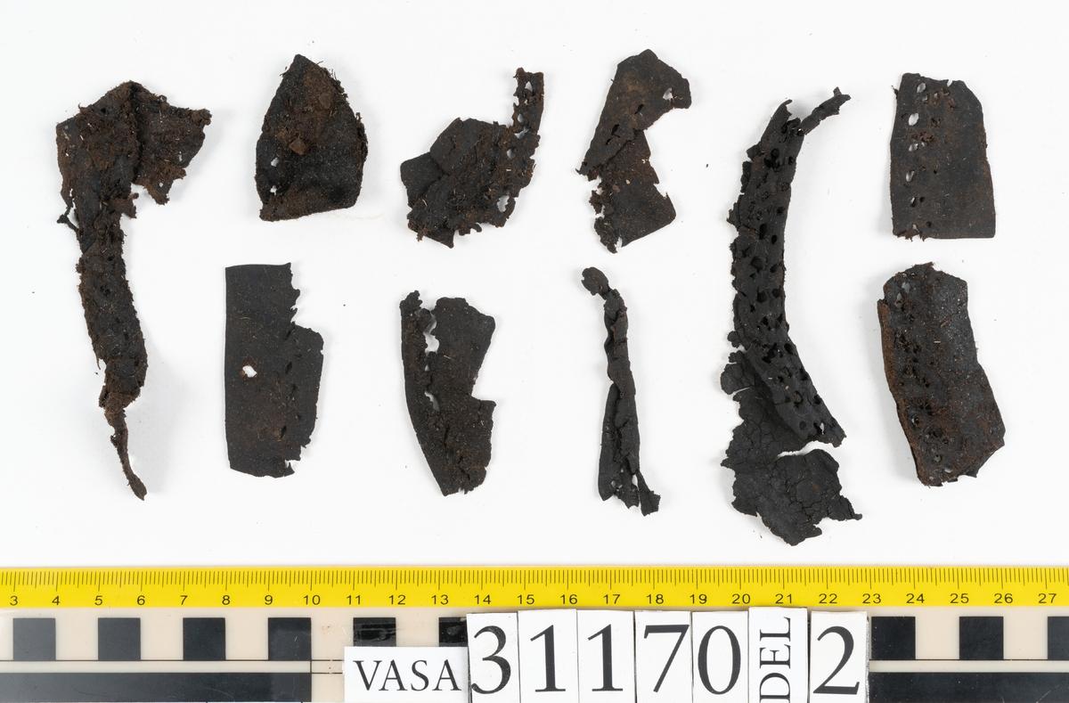 Ett 90-tal delar och fragment från sko i form av, sulor, inlägg, ovanläder, klacklappar, sidostycken, bakkappa mm. Två stycken sidostycken. Sidostyckena har slutit om hälpartiet och suttit fästade mitt bak på skon. Sidostyckena är skurna med en kort slejf. I slejfändarna finns snörhål. På bägge sidostyckena finns parallellt ritsade, dekorativa linjer. Linjerna löper längs med slejfen, ena kortsidan och den övre långsidan. På insidan av sidostyckena löper stygn efter fastsättningen av bakkappan. En bakkappa. bakkappan har suttit fästad på insidan skons sidostycket och på sätt förstärkt hälpartiet. Lädret är kladdigt med välbevarat.
