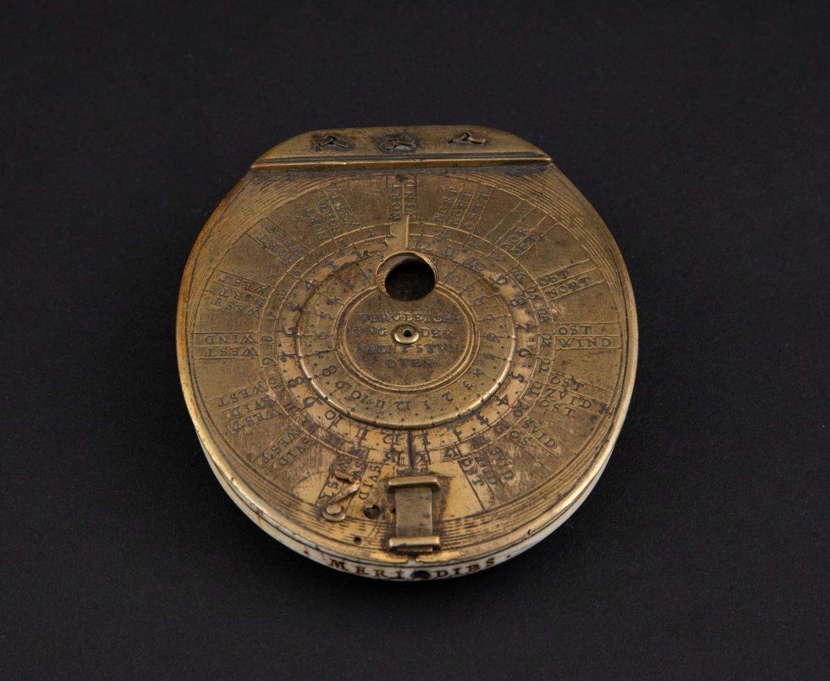 Solur i messing og elfenben. Oval form med elfenbensskive med kompass og inndeling med arabiske tall. På hver side messinglokk, det øvre hengslet og med svingbar midtskive med viser. Innskrifter på inn- og utsiden av soluret.