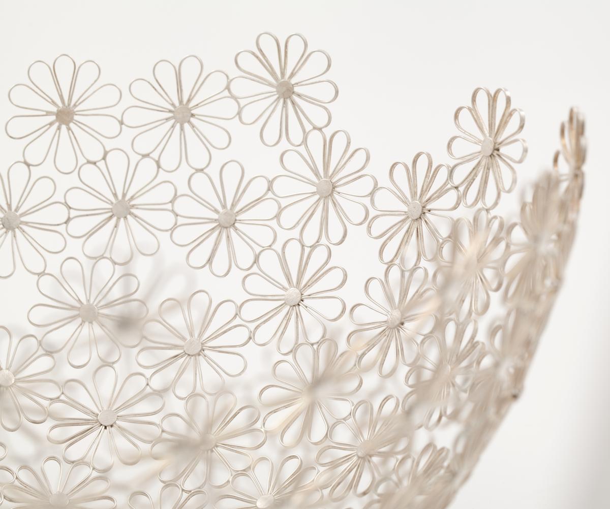 Halvkuleformet bolle i sølvfiligran, som danner et nettverk bestående av stiliserte blomsterformer.