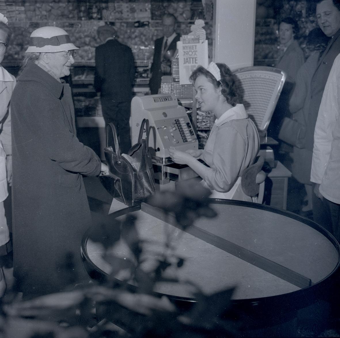 Bild tagen i samband med invigning av Konsum. En kvinna vid kassan bland människor.