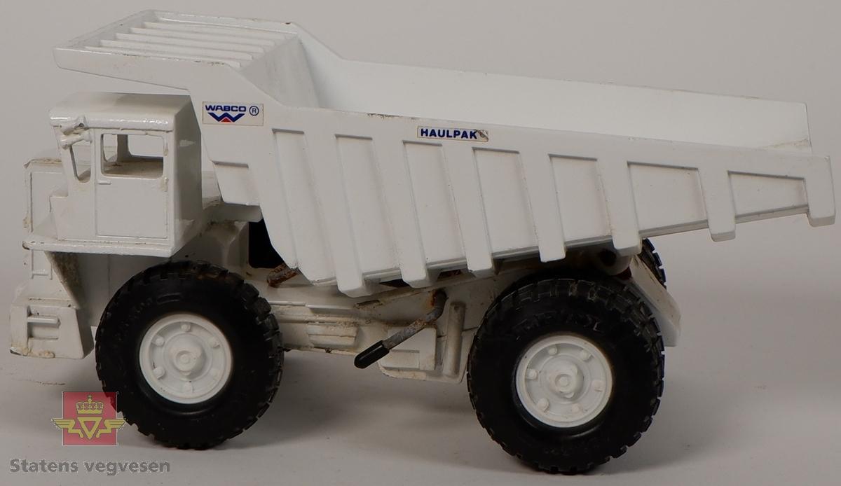 Miniatyrmodell av en Haulpak dumper. Maskinen er produsert i metall med hjul av plast og gummi. Dumperen er hvit med klistremerker som har påskriftene HAULPAK og WABCO.