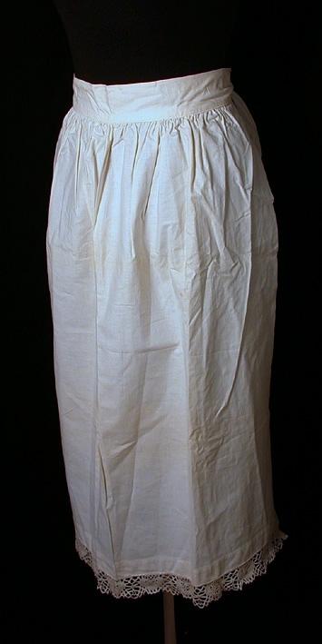 Vitt förkläde i bomullstyg. Ett stycke rynkat mot 50 mm bred linning som fortsätter 200 mm utanför förklädet. I ändarna fastsytt 50 mm brett fållat band 800 mm för knytning i ryggen. I nederkant 40 mm bred maskintillverkad spets.